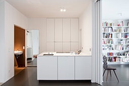 White fitted cupboards and sliding door in interior kitchen without windows
