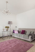 Scatter cushions on grey sofa, silver standard lamp and serving trolley, dusky-pink rug and chandelier in living room