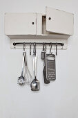 Wall-mounted cabinet with kitchen utensils hung from hook rail below