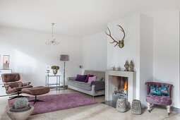 Lilac easy chair next to fireplace, grey sofa, standard lamp, serving trolley and classic chair in living room