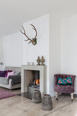 Fliederfarbener Polstersessel, Kamin und graues Polstersofa im Wohnzimmer