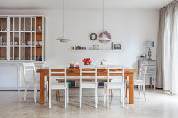 White dresser with glass doors and wooden table with white chairs in dining area