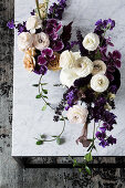 Dramatic table arrangements in white and violet on a marble table