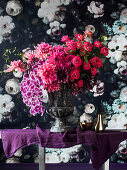 Opulent bouquet of flowers in an amphora in front of floral wallpaper