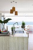 Kücheninsel mit Steinplatte; Blick auf die Terrasse und das Meer