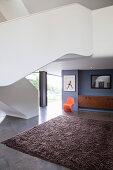 Orangefarbener Designerstuhl unter futuristischer Treppe