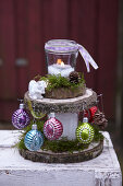 Festive arrangement of slices of tree trunk decorated with candle lantern and Christmas-tree baubles