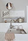 Sink, silver pots and shaving mirror in bathroom with white wall tiles
