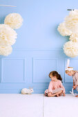 Two girls with a bunny in the room with light blue wall