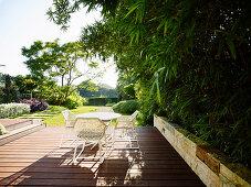 Weißer Tisch und Stühle auf Holzterrasse, seitlich Bambuspflanze als Sichtschutz