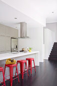 Red metal stools on the kitchen island in the open kitchen