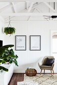 Armchair, sideboard and houseplants in living room with white wooden panelling