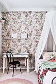 White desk and black chair next to child's bed with canopy in girl's bedroom with floral wallpaper