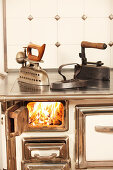 Antique irons heating on hob of wood-fired cooker