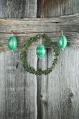 Box wreath and hand-painted green Easter eggs on rustic wooden wall