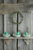 Hand-painted Easter eggs in willow nests on rustic wooden shelf