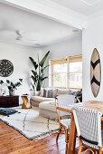 View past dining table into living room with ethnic accessories and houseplants