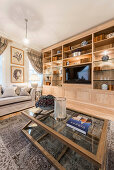 Illuminated fitted cabinets in classic living room in earthy shades