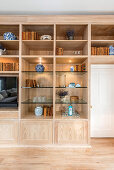 Wooden fitted cabinets with indirect lighting and glass shelves