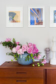 Natural-style arrangement of peonies on sideboard