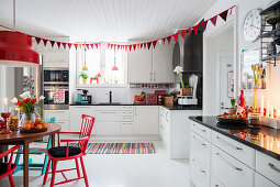 Red Christmas decorations in white kitchen-dining room