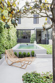 Rattan lounger on concrete terrace with pool in background