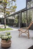 Hydrangeas and rattan armchair on concrete terrace
