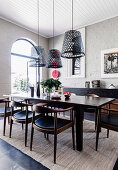 Dark dining table with chairs, hanging lamps from old fishing baskets in the room with a white-painted brick wall