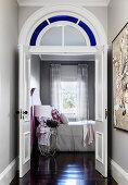 View through the open door into the bedroom with black floorboards