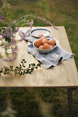 Bowl of eggs on cloth on table in garden