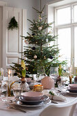 Festively set dining table in front of Christmas tree