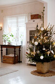Decorated Christmas tree in front of glass-fronted cabinet in Scandinavian dining room with white wooden floor