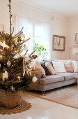 Decorated Christmas tree next to grey sofa in living room