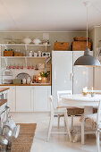 Round dining table and chairs in white, rustic kitchen