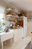 White table, kitchen counter and fridge in rustic kitchen