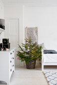 Decorated Christmas tree and white chest of drawers in white room