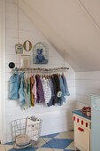 Child's clothes on DIY clothes rack in attic room with blue-and-white chequered floor