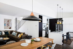 Long dining table in front of lounge with upholstered sofa, black-and-white kitchen with counter in open living room in background