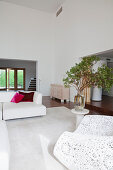 White designer armchair with crochet effect, vase of leafy branches on side table and white sofa in open-plan interior