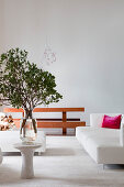 Vase of leafy branches on side table, white sofa and dining table with benches in open-plan interior
