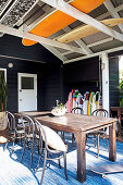 Vintage wooden table with bentwood chairs and surfboard collection on wooden terrace