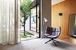 Grauer Designersessel und Stehlampe vor Terrassentür