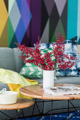 Vase with leaf sprigs on coffee table, sofa in front of colorful wallpaper