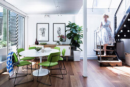 Replica of classic table with lime green chairs in open dining area, woman on stairs