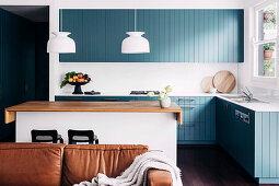 Blick über Ledersofa auf Einbauküche mit blau-grau lackierter Holzfront und Kücheninsel