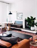 Runder Tisch mit Sitzbank, Kamin, Couchtisch und Ledercouch im Wohnzimmer