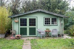 Grünes Gartenhaus im herbstlichen Garten