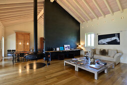 Low coffee table, couch, suspended fireplace and floating shelf on black partition in open-plan interior
