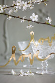 Gold paper lettering reading 'love' in front of old wine glasses
