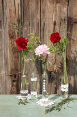Peonies in glass bottles with lacy paper trim